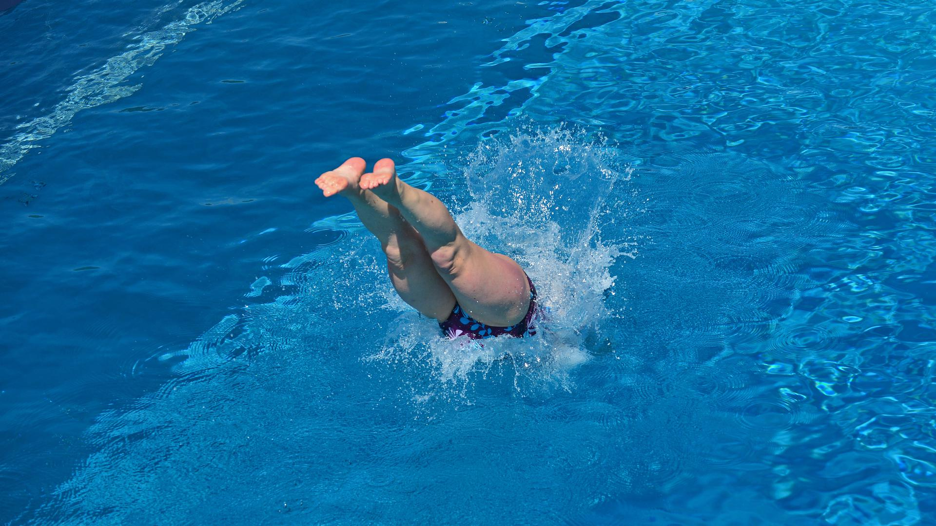 Eine Frau springt in einem Freibad ins Wasser.