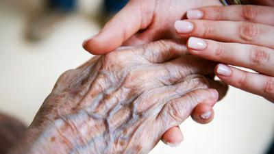 Eine Frau hält die Hand eines Senioren.