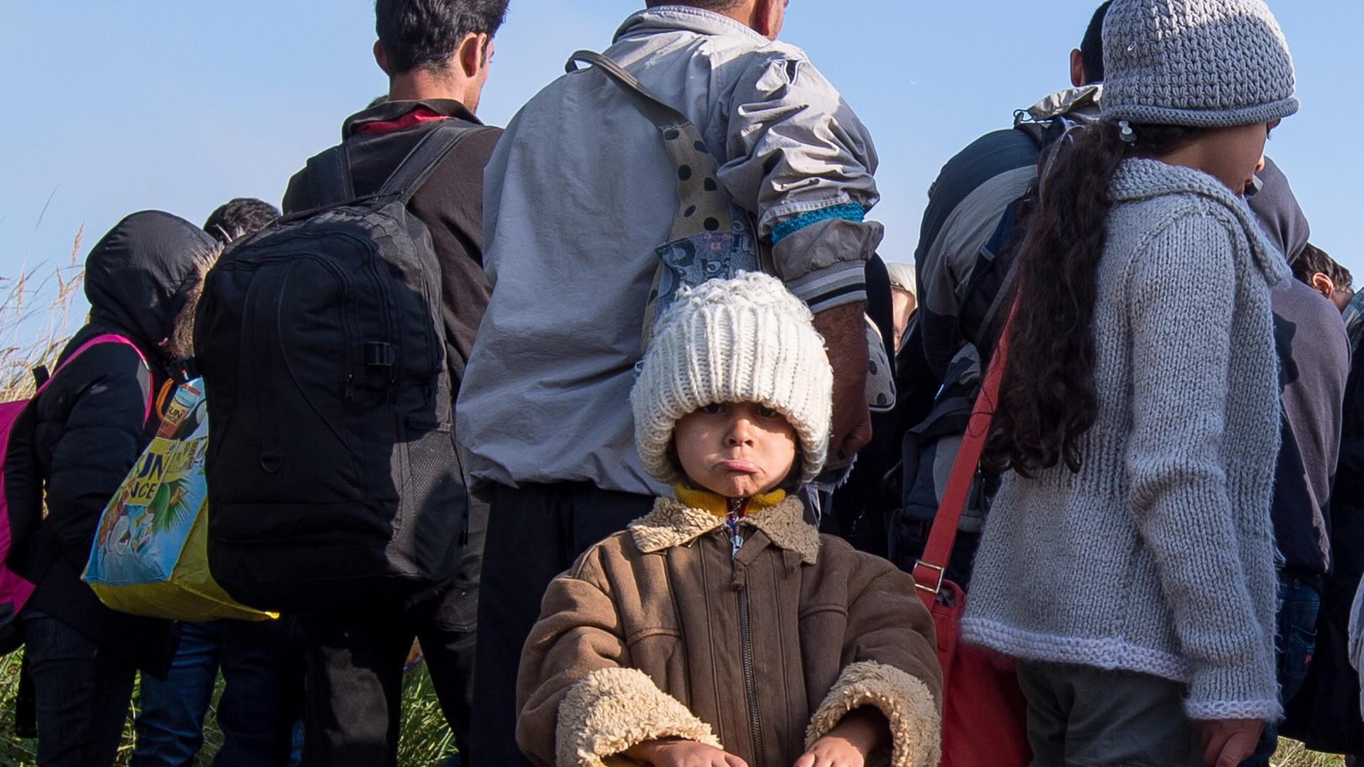 ARCHIV - Flüchtlinge, die zuvor am Bahnhof Schönefeld (Brandenburg) angekommen waren, warten am 10.09.2015 an einem Sammelplatz unweit des Bahnhofes. (zu dpa «Familiennachzug: Neue Flüchtlingswelle oder leistbare Herausforderung» vom 19.10.2017) Foto: Patrick Pleul/dpa-Zentralbild/dpa +++(c) dpa - Bildfunk+++ | Verwendung weltweit