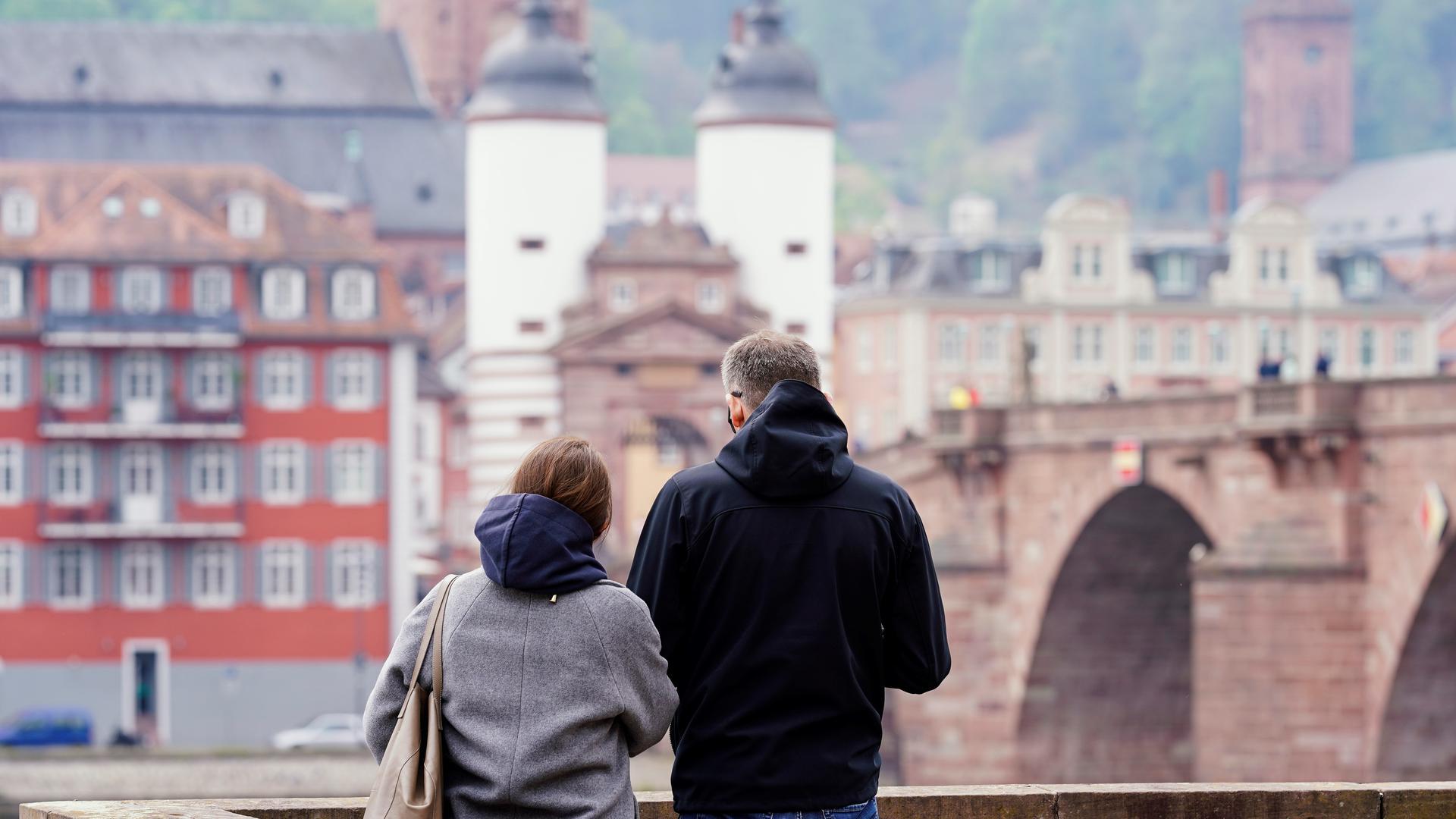 Ein Mann und eine Frau stehen an der Alten Brücke. Heidelberg kann als erste Stadt im Südwesten die Bundesnotbremse lockern.