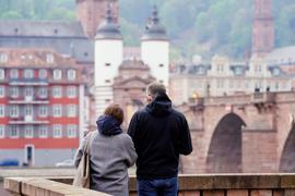 Ein Mann und eine Frau stehen an der Alten Brücke. Heidelberg kann als erste Stadt im Südwesten die Bundesnotbremse lockern. In fast allen Land- und Stadtkreisen Baden-Württemberg gelten derzeit noch die verschärften Regelungen des Bundes. +++ dpa-Bildfunk +++