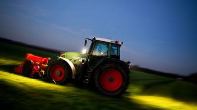 Ein Landwirt mäht mit seinem Traktor eine Wiese.