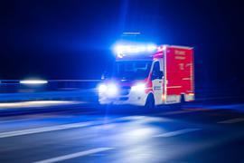 Ein Rettungswagen der Feuerwehr fährt mit Blaulicht durch eine Straße.