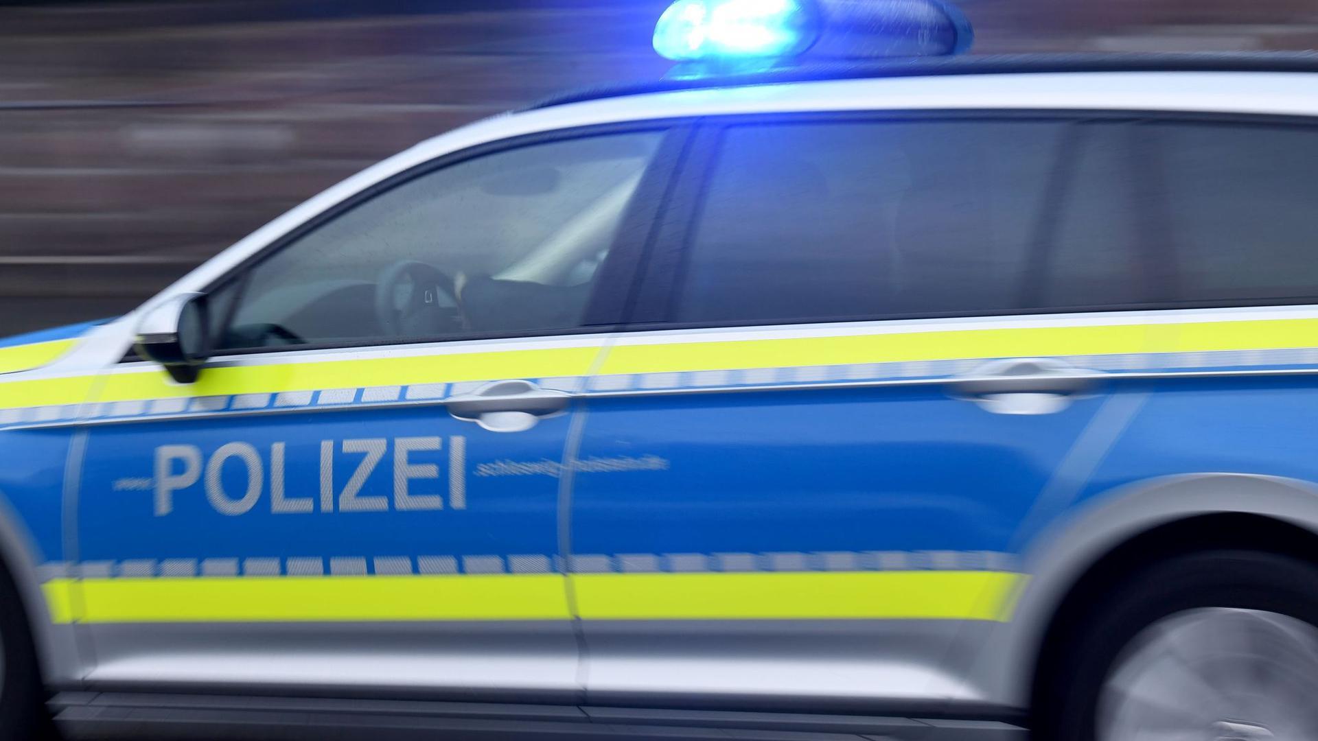 Ein Streifenwagen mit eingeschaltetem Blaulicht fährt über eine Straße.