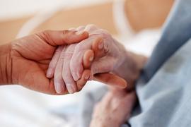Eine Pflegerin hält in einem Altenheim die Hand einer Bewohnerin.