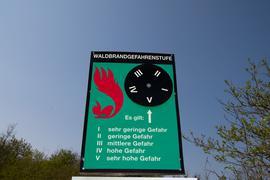 Ein Schild an einem Waldweg weist auf die Waldbrandstufe fünf hin.
