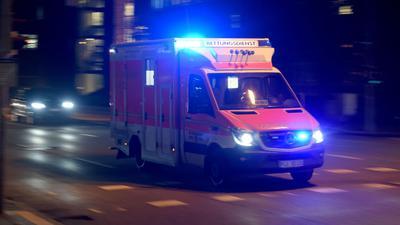Ein Rettungswagen fährt abends mit Blaulicht über die beleuchtete Straße.