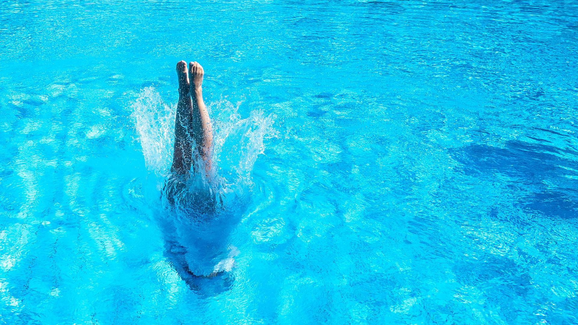 Eine Frau taucht in einem Stuttgarter Schwimmbad ins Becken ein.