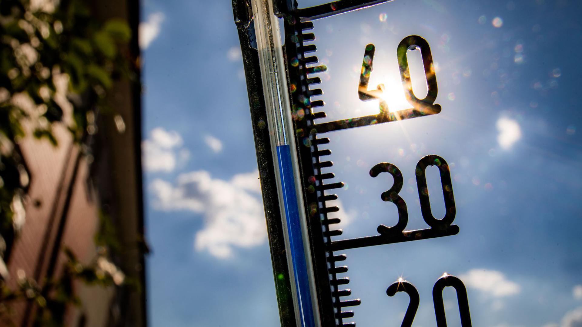 Ein Thermometer an einer Hauswand klettert in Richtung der 40-Grad-Marke.