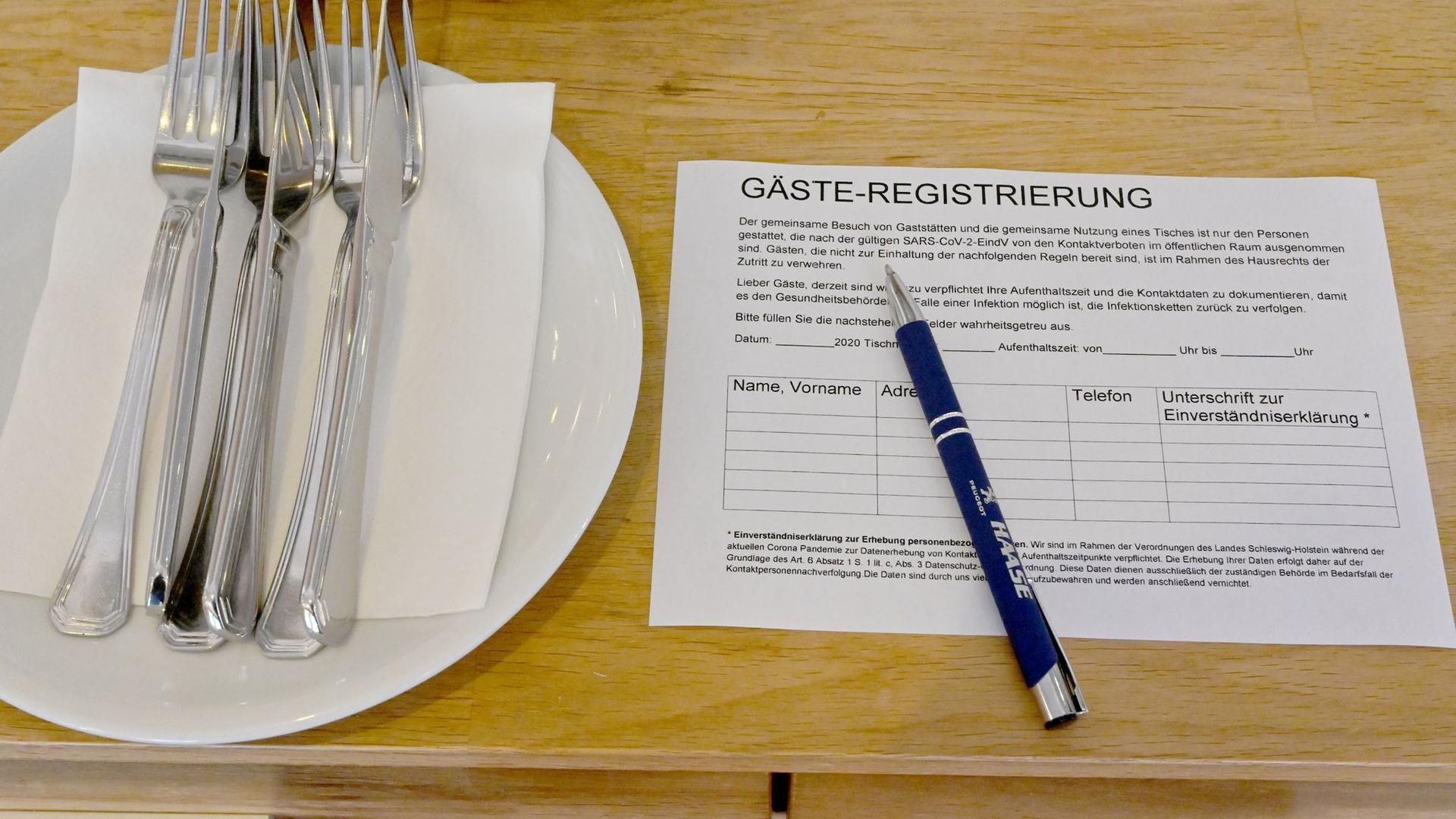 Ein Zettel für die Gäste-Regstrierung liegt in einem Restaurant auf einem Tisch.