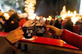 Zwei Besucherinnen stoßen in der Weihnachtszeit 2019 auf einem Weihnachtsmarkt mit Glühwein an.