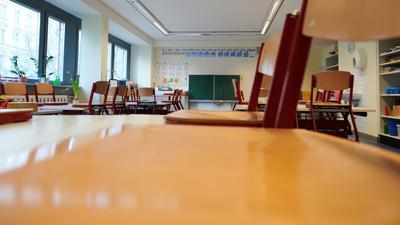 In einem Klassenzimmer sind die Stühle auf die Tische gestellt.