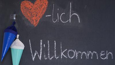 """""""Herzlich Willkommen"""" steht zu Beginn des neuen Schuljahrs mit Kreide auf der Tafel eines Klassenzimmers."""