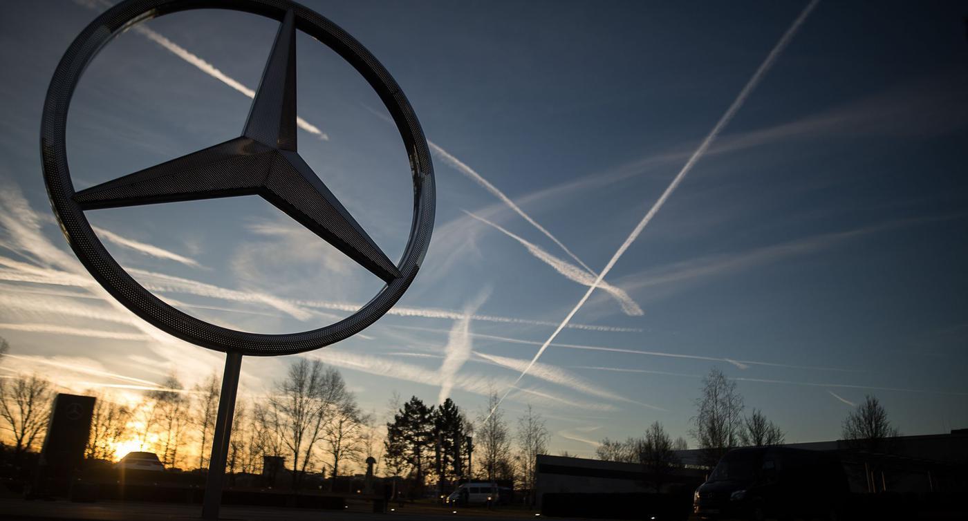 Die Sonne geht hinter einem Mercedes-Stern auf dem Mercedes-Benz-Werk auf.