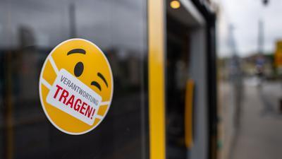 """Ein Smiley-Aufkleber mit einem Mundschutz und der Aufschrift """"Verantwortung tragen"""" klebt an einer Scheibe einer Straßenbahn."""