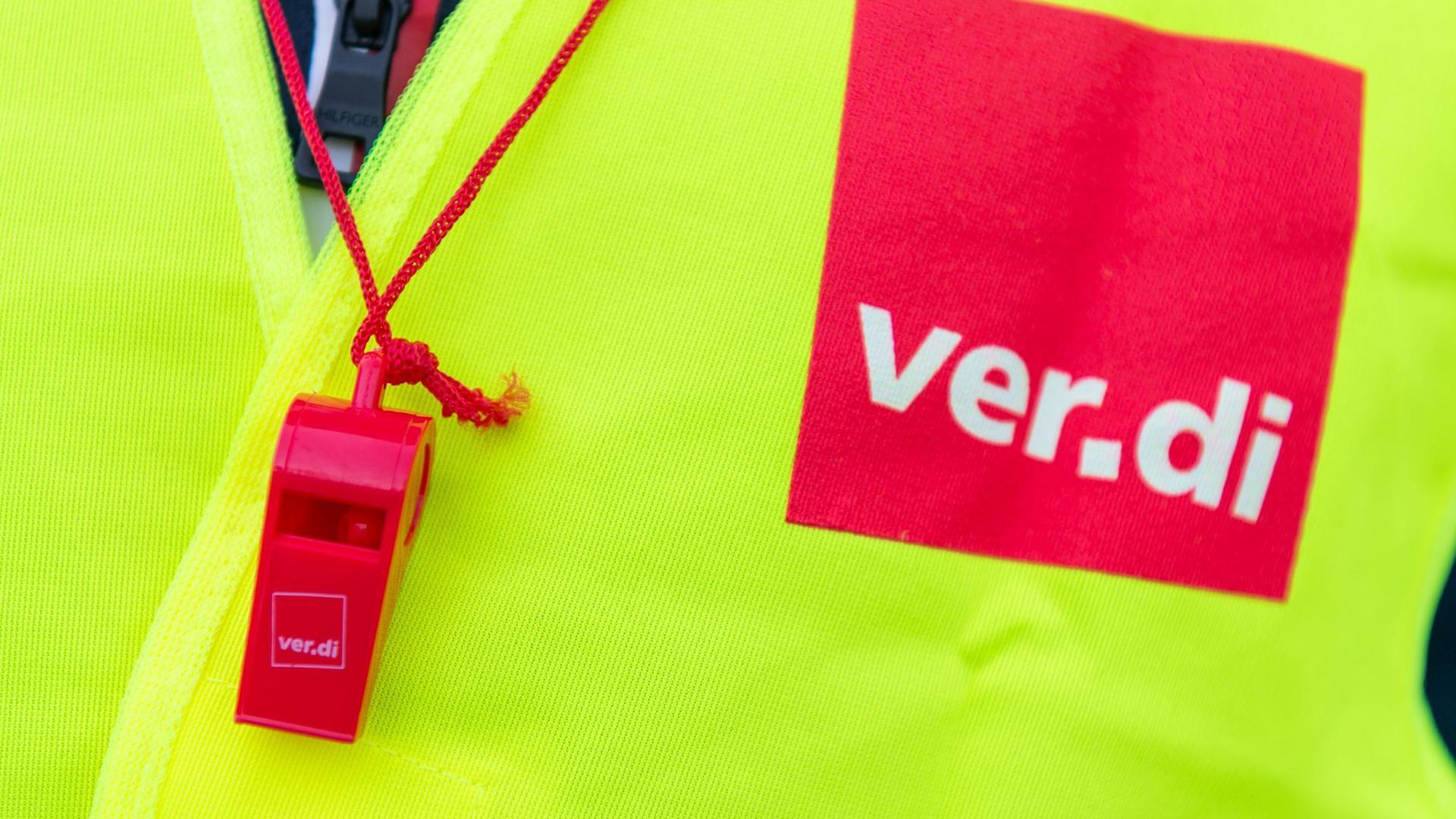 Ein Streikender mit einer Warnweste mit dem Verdi-Logo und einer roten Trillerpfeife.