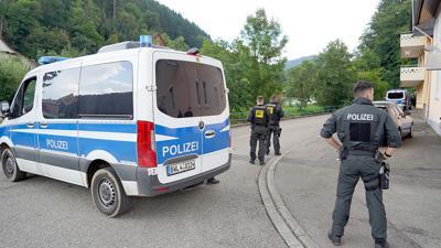 Polizisten stehen bei Oppenau vor einer Einfahrt in ein Waldgebiet.