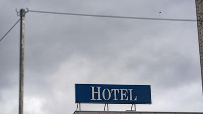 """Das Wort """"Hotel"""" steht auf einer Leuchttafel auf einem Hotel."""