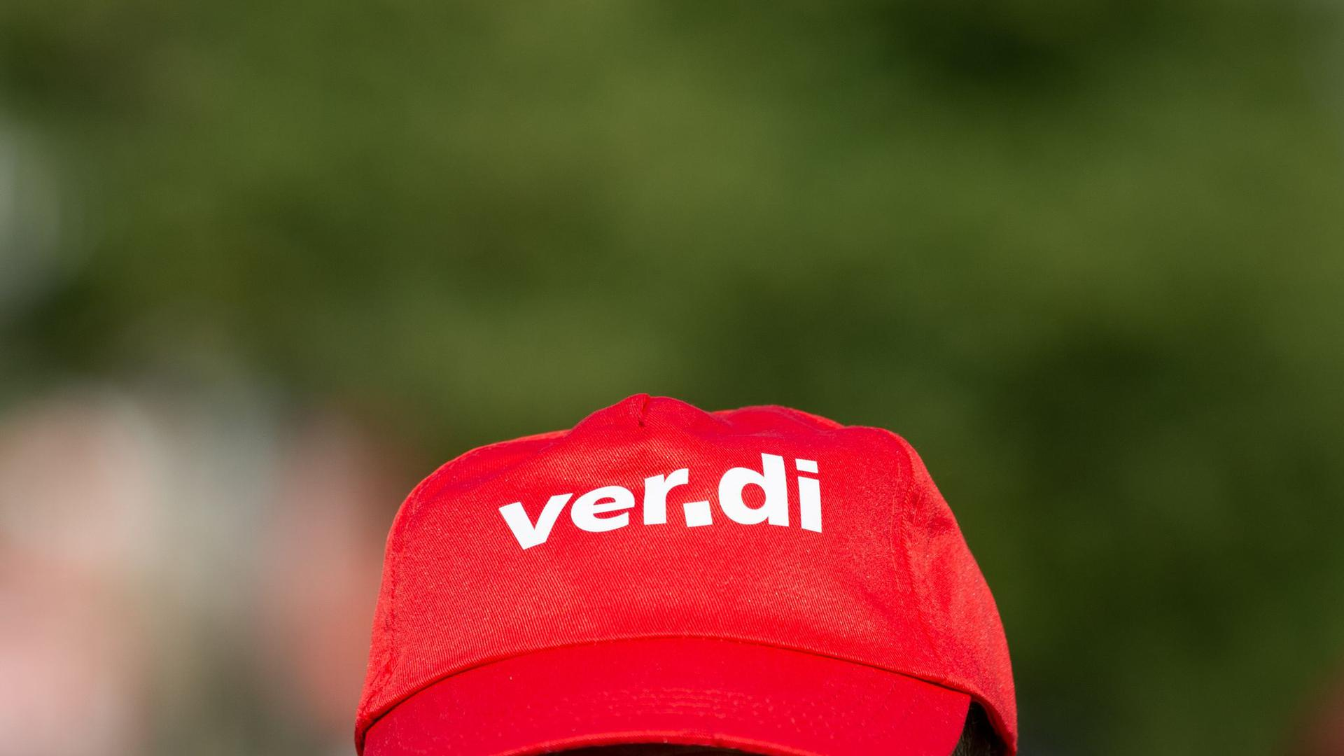 Ein Mann trägt beim Warnstreik eine Mütze mit dem Verdi Logo.