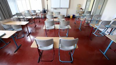 Die Stühle in einem leeren Klassenzimmer stehen auf den Tischen.