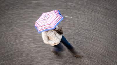 Eine Frau geht bei regnerischem Wetter über eine Straße.