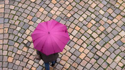 Eine Frau geht mit einem Regenschirm auf einer Straße mit Kopfsteinpflaster entlang.