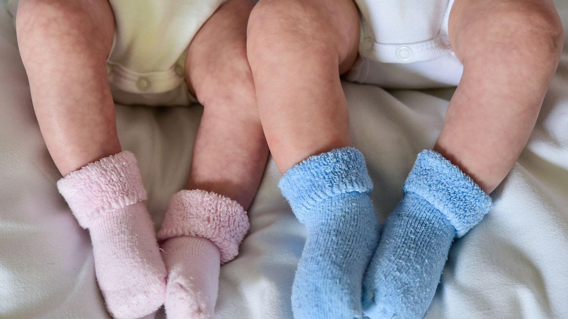 Rosa und blaue Söckchen für ein Mädchen und einen Jungen und die nackten Babybeine von Zwillingen.