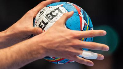 Ein Handballer hält den Spielball in den Händen.