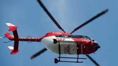 Ein Rettungshubschrauber fliegt über einen Flugplatz.