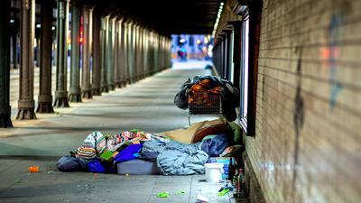 Obdachlose liegen unter einer Eisenbahnunterführung.