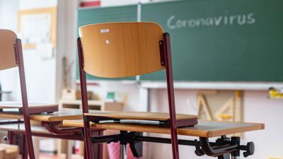 """""""Coronavirus"""" steht auf einer Tafel in einem leeren Klassenzimmer."""