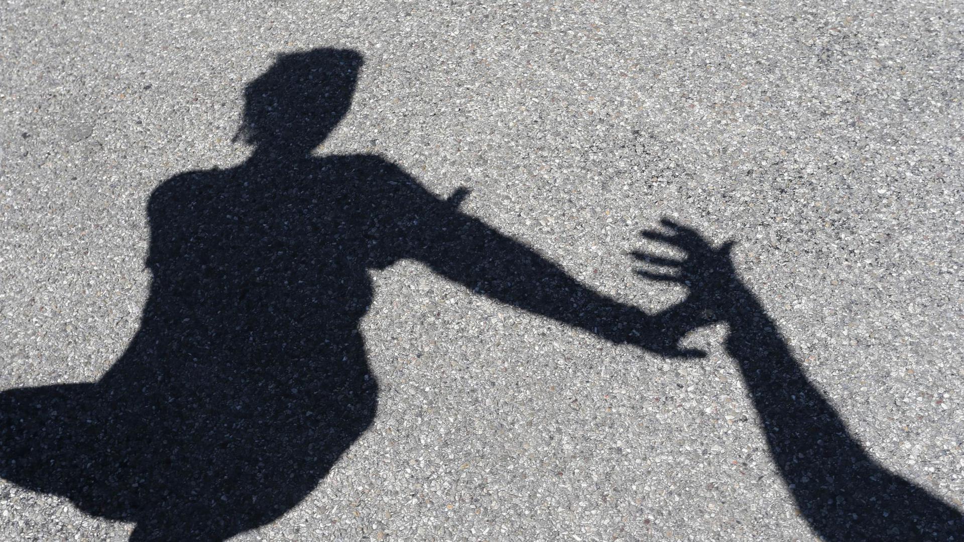 Eine Frau, nach der ein Mann greift, beide im Schattenriss.