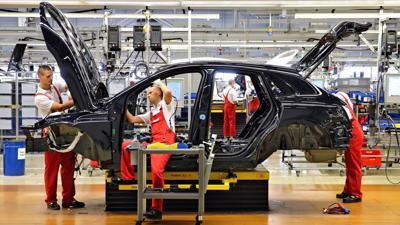Mitarbeiter montieren einen Pkw in der Produktion der Porsche AG.