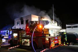 Einsatzkräfte der Feuerwehr löschen einen Brand in einem Mehrfamilienhaus.
