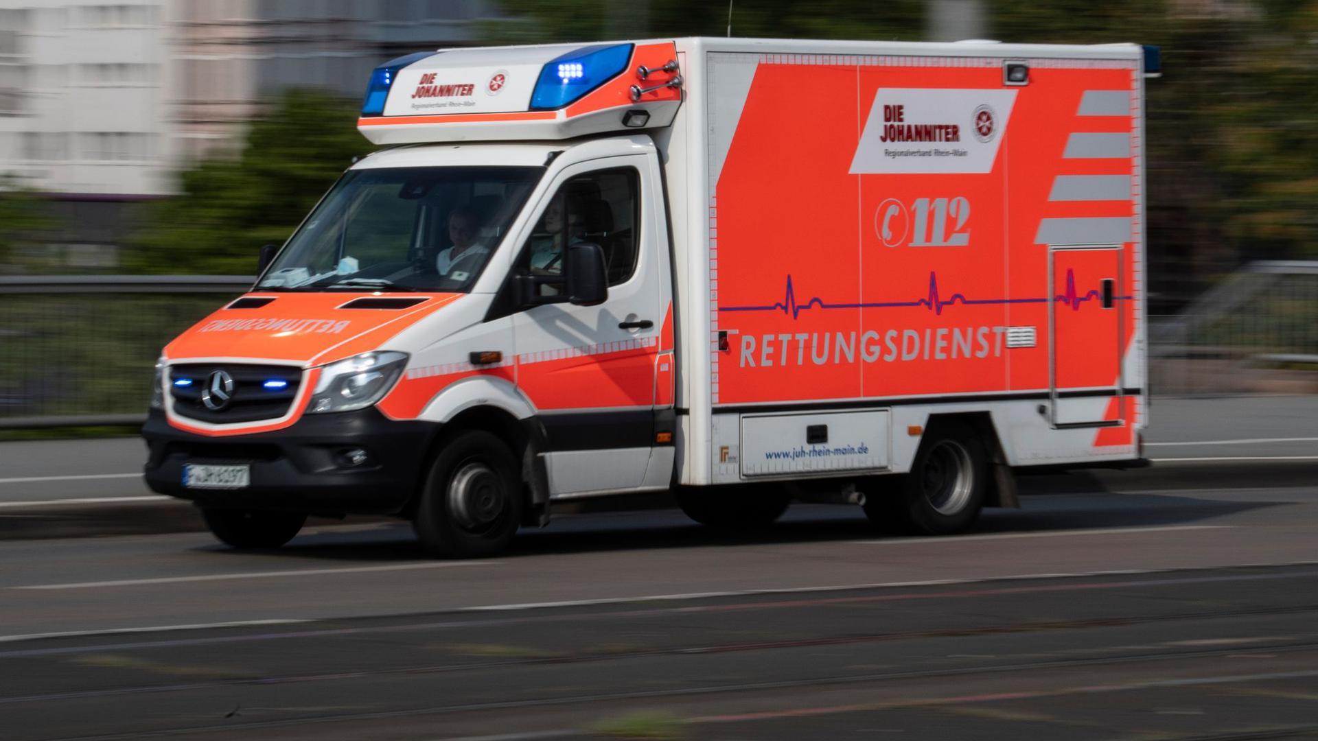 Mit eingeschaltetem Blaulicht fährt ein Rettungswagen eine Straße entlang.