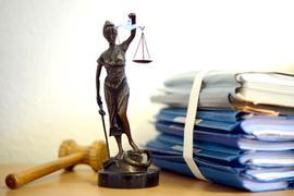 Eine modellhafte Nachbildung der Justitia steht neben einem Holzhammer und einem Aktenstapel.