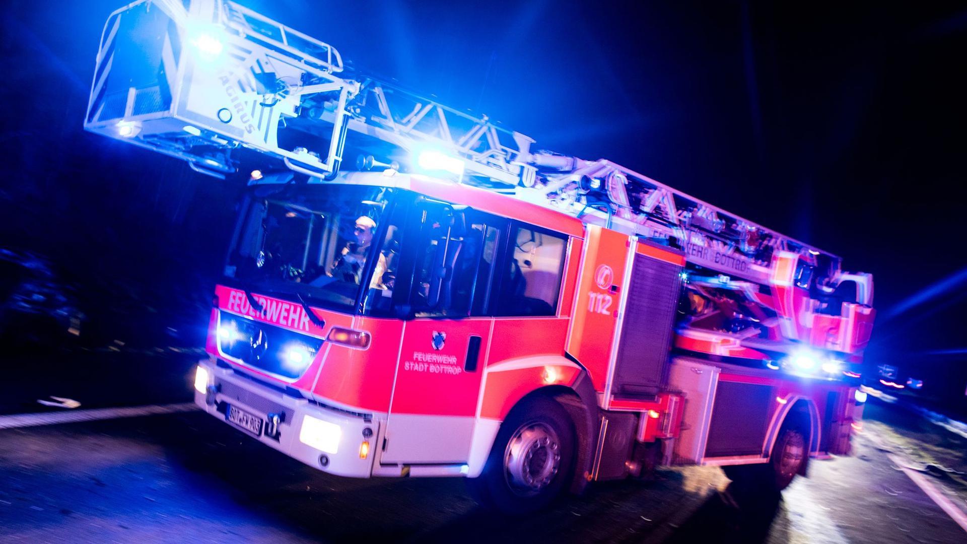Ein Drehleiterwagen der Feuerwehr fährt mit Blaulicht an einer Unfallstelle vorbei.