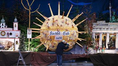 Ein Helfer montiert in der ein überdimensionales Modell eines Corona-Virus in der Martinuskirche.