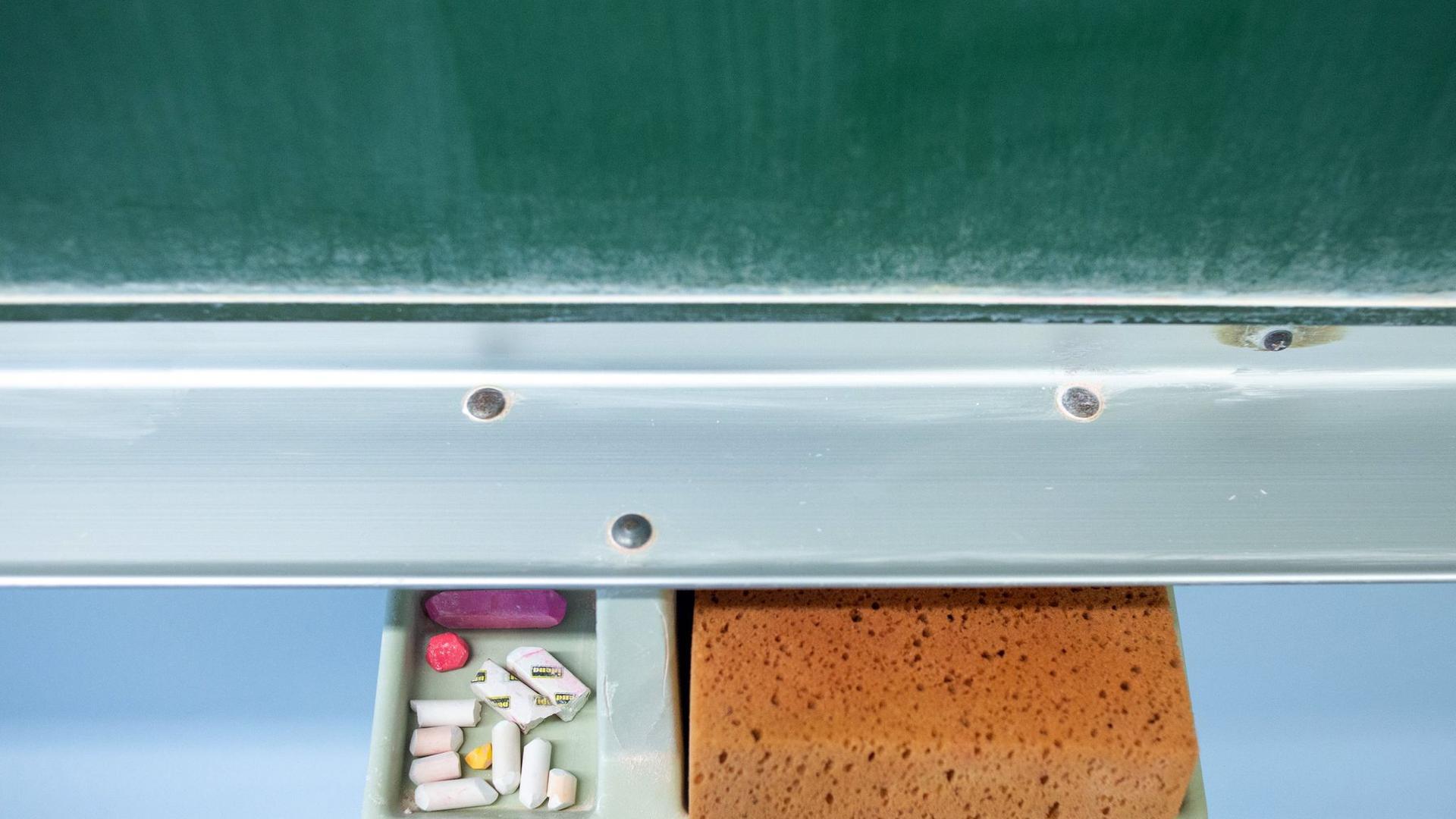 Schwamm und Kreide liegen in einem Klassenraum unter einer Tafel.