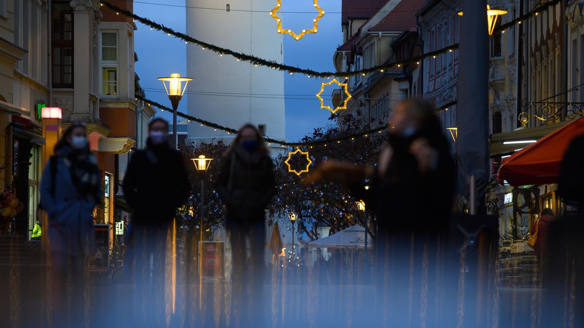 Passanten mit Mund-Nasen-Schutz gehen durch eine festlich dekorierte Fußgängerzone.