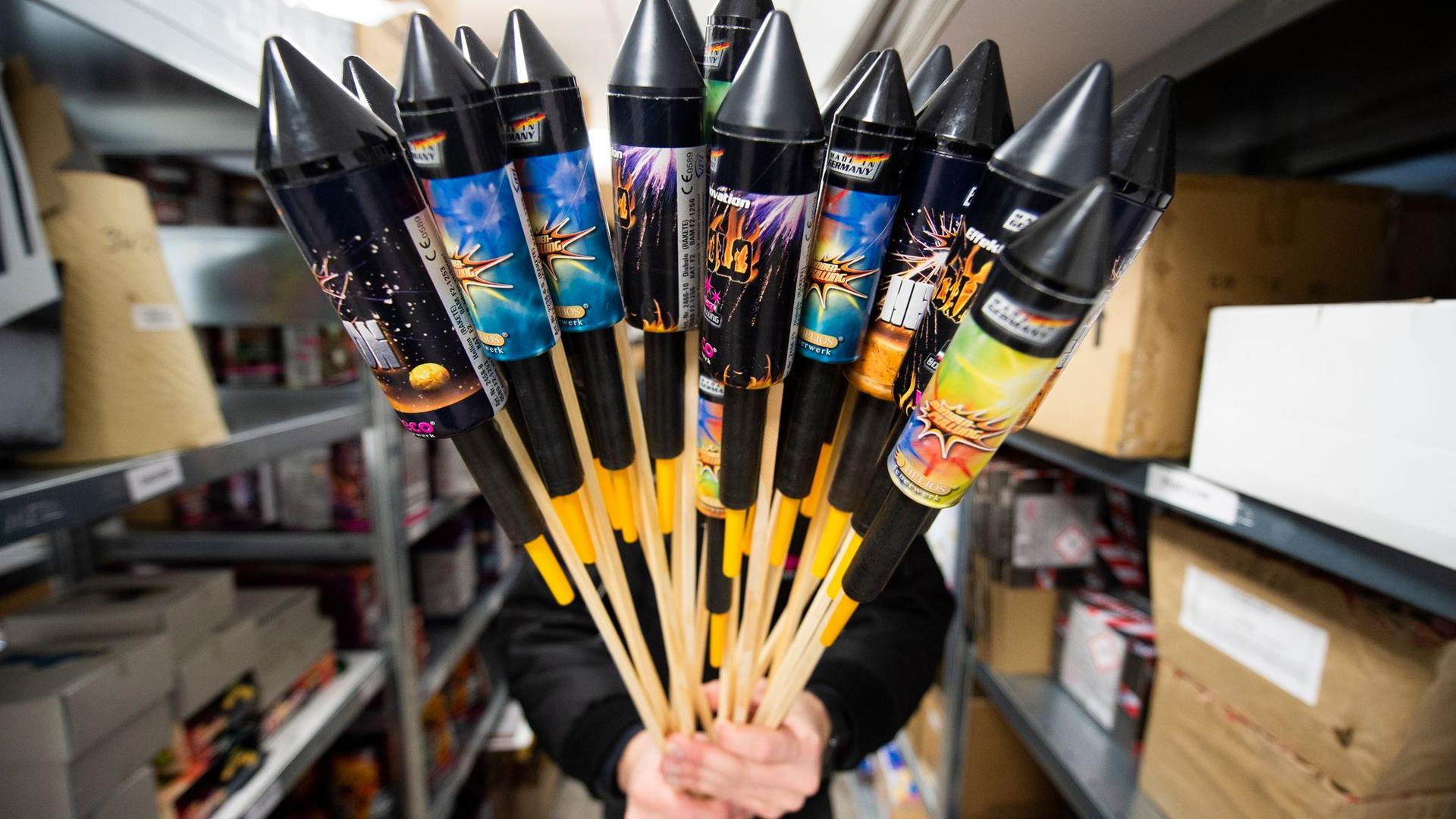 Ein Mitarbeiter von Weco, Hersteller von Feuerwerk, hält in einem Lagerraum Silvesterraketen.