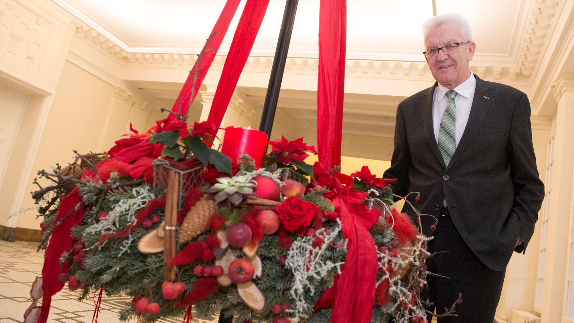 Ministerpräsident Winfried Kretschmann (Grüne) steht im Staatsministerium an einem Adventskranz.