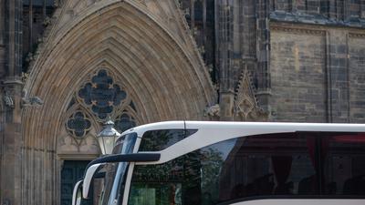 Ein Reisebus steht vor einer Kirche.