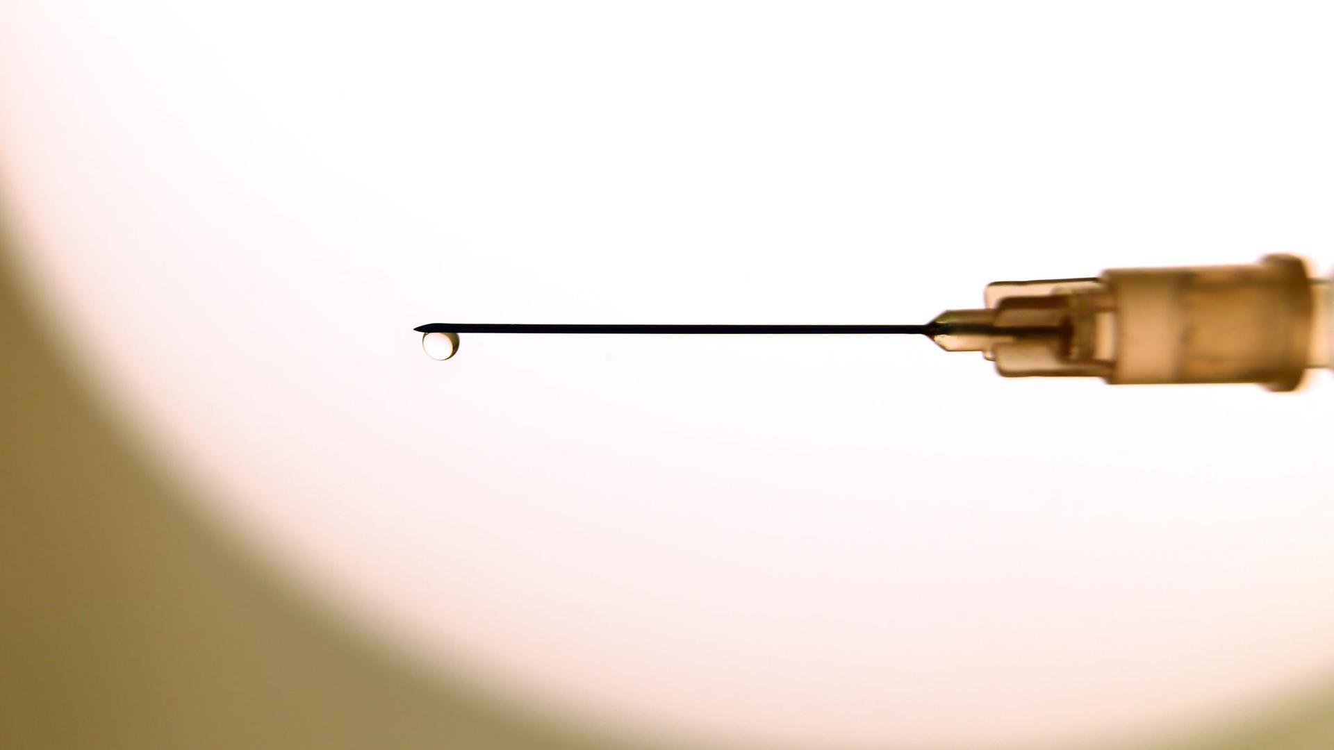 Eine Flüssigkeit tropft aus der Kanüle einer Spritze.