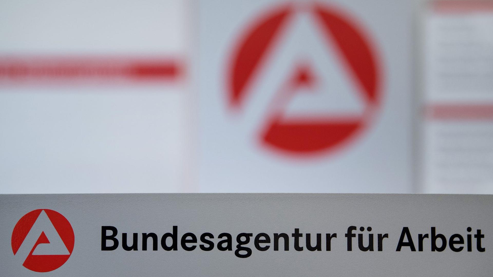 Der Schriftzug der Bundesagentur für Arbeit steht vor einem Logo der Bundesagentur.