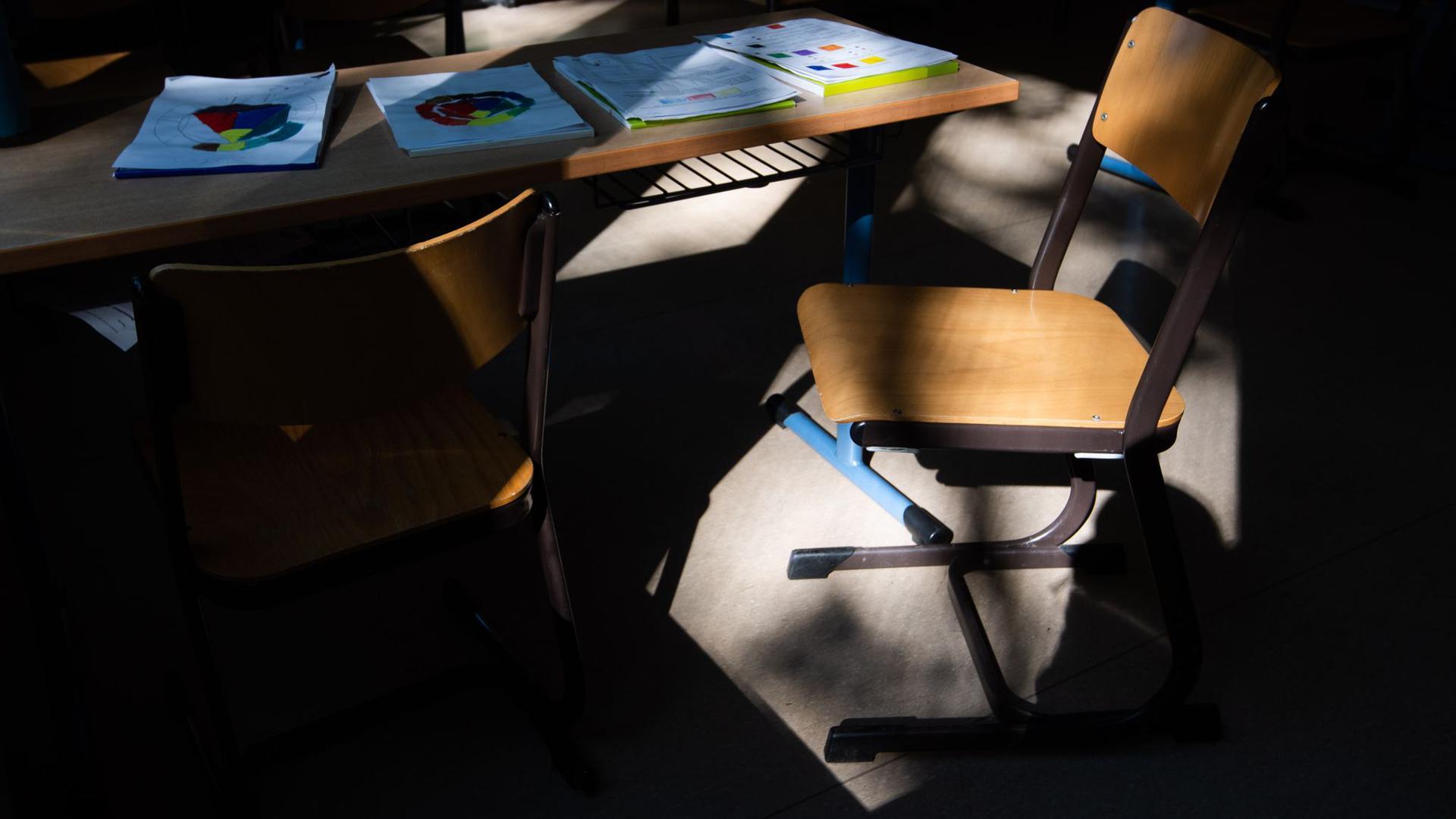 Ein Stuhl steht in einem leeren Klassenraum auf einem Tisch.