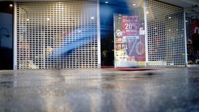 Ein Passant fährt auf seinem Skateboard an einem geschlossenen Ladengeschäft vorbei.