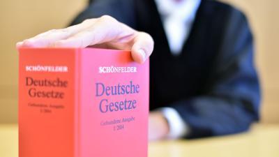 An der Richterbank eines Sitzungssaals sitzt ein Richter hinter einem Buch mit Deutschen Gesetzen.