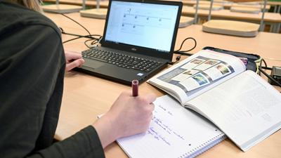 Eine Schülerin lernt während der Notbetreuung im Klassenzimmer am Laptop.