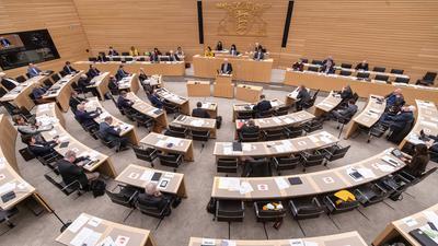 Abgeordnete sitzen bei einer Sitzung des Landtags im Plenarsaal.